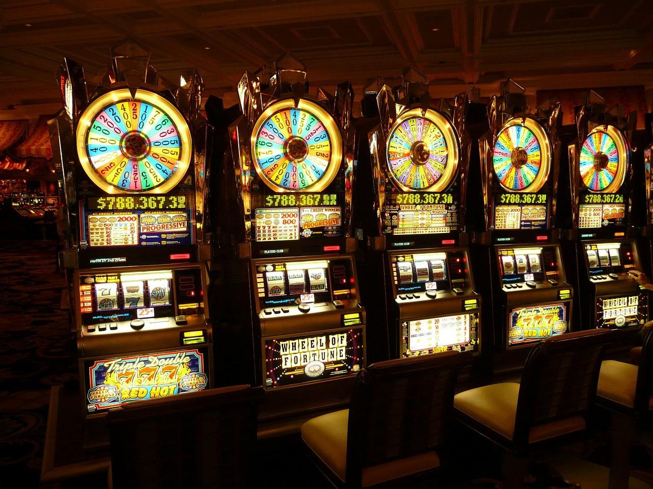 Billedet viser 5 spillemaskiner på et casino, hvilket forbinder billedet med spilleautomater